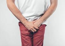 握他的阴茎有在白色背景的一个人 要去洗手间 库存照片