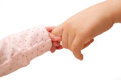 握更老的孩子的手指的新出生的婴孩。 库存图片