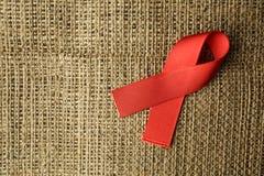 援助在粗麻布, HIV丝带的红色丝带 库存图片