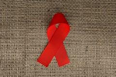 援助在粗麻布, HIV丝带的红色丝带 免版税库存照片