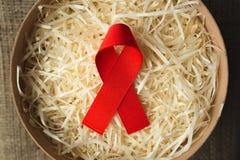 援助在粗麻布, HIV丝带的红色丝带 免版税库存图片