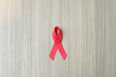 援助天和心脏病巨蟹星座了悟,在木背景的红色丝带支持的人居住的 免版税库存图片
