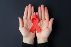 援助红色丝带在棕榈和在黑背景, HIV ribbo 库存照片