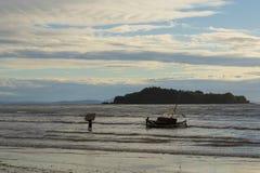 搁浅在低潮海的水手一条小船日落的 免版税库存图片