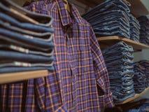 搁置jeanswear 在牛仔布背景的减速火箭的格子花呢上衣  免版税库存照片