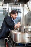 搅动一个巨大的罐炖煮的食物或砂锅的厨师 免版税库存图片