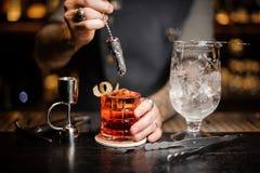 搅动与一把装饰匙子的专业侍酒者一个新鲜的红色鸡尾酒 库存照片