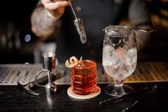 搅动与一把装饰匙子的侍酒者一个新鲜的红色鸡尾酒 库存照片
