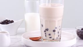 搅动在玻璃杯子的鲜美台湾普遍的饮料珍珠粉珍珠泡影奶茶在明亮的大理石桌白色盘子,自创浓缩 股票视频