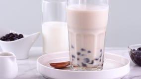 搅动在玻璃杯子的鲜美台湾普遍的饮料珍珠粉珍珠泡影奶茶在明亮的大理石桌白色盘子,自创浓缩 影视素材