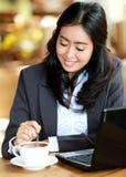 搅动她的咖啡的女实业家 免版税库存图片