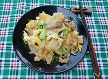 搅动油煎的面条用鸡蛋、猪肉、绿色vetgetables和甜点 库存照片