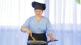 搅动菜的妇女油煎在有鸡的一个平底锅 股票录像