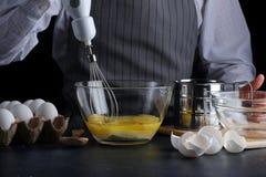 搅拌器和面团 饼或蛋糕或者乳酪蛋糕概念食谱在黑暗的 免版税库存图片