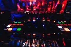 搅拌器DJ有控制的一个混合的音乐的夜总会和按钮在党 图库摄影