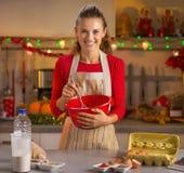 搅拌在圣诞节的愉快的年轻主妇面团装饰了厨房 库存图片