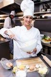 搅拌碗鸡蛋的愉快的厨师 库存图片