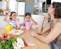 搅拌鸡蛋的母亲和孪生在厨房里 免版税库存图片