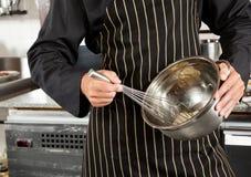 搅拌鸡蛋的男性厨师在厨房里 免版税图库摄影