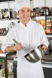 搅拌鸡蛋的男性厨师在厨房里 库存照片