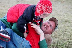 搏斗在草的爸爸和儿子 免版税库存图片