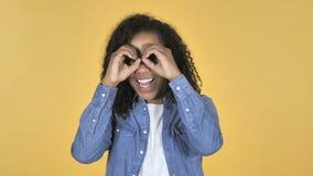 搜寻与手工制造双筒望远镜的非洲女孩隔绝在黄色背景 股票录像