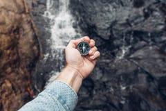 搜寻与指南针在瀑布,观点射击的人探险家方向 免版税库存照片