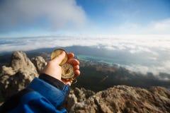 搜寻与金黄指南针的探险家人观点照片方向在他的在云彩上的手上与秋天 免版税图库摄影