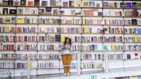 搜寻书的妇女在图书馆里 影视素材
