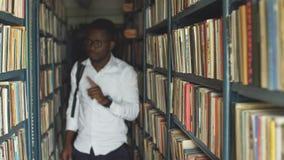 搜寻书的白肤金发的老师在图书馆里在学校 股票视频