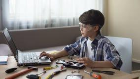 搜寻关于在膝上型计算机的硬盘驱动器指示,爱好的安全玻璃的好奇男孩 影视素材