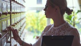 搜寻卡片数据库内阁的妇女在图书馆 影视素材