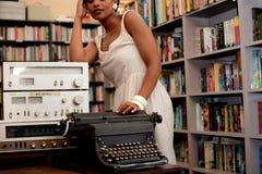 搜寻在架子的书的夫人 免版税库存图片