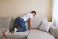 搜寻在沙发后的膝盖的有胡子的人丢失了事 免版税库存图片