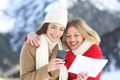 搜寻在线的两个愉快的游人在寒假 库存照片