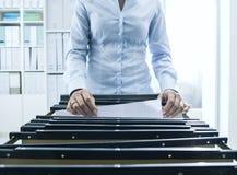 搜寻文件的办公室工作者在档案里 免版税库存图片
