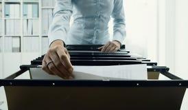 搜寻文件的办公室工作者在档案里 免版税库存照片