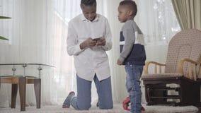 搜寻某事在手机和她的小逗人喜爱的儿子的美国非洲妇女感兴趣对舒适客厅 股票录像
