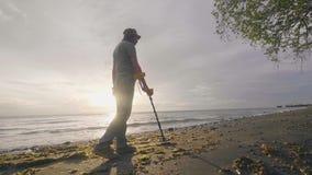 搜寻贵重物品的人在沙子下使用走与他的在热带海滩的狗的金属探测器在日出 影视素材