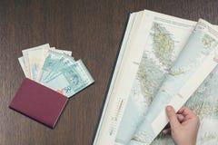 搜寻马来西亚的地图的一只女性手计划一次新的旅行 旅行护照和马来西亚人金钱在背景 图库摄影