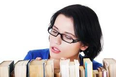 搜寻一本有趣的书的少妇 免版税库存照片