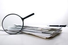 搜寻与放大镜,寻找在书的信息,图纸,杂志 审计检查 复制空间文本 免版税库存图片