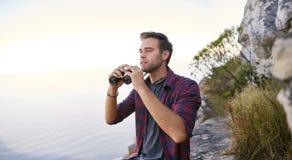 搜寻与他的双筒望远镜的视域的年轻人户外 库存照片