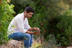 搜寻互联网覆盖面的年轻拉丁人室外, 免版税库存照片