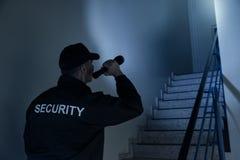 搜寻在与手电的楼梯的治安警卫 图库摄影