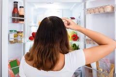 搜寻在冰箱的食物的迷茫的妇女 免版税库存图片