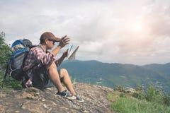 搜寻在地图的背包徒步旅行者人正确的方向 免版税库存图片