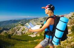 有地图的活跃女孩在山 免版税库存照片