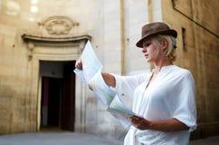 搜寻在地图路的时髦的妇女对某事,当站立在建筑纪念碑附近户外时 库存照片