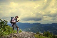 搜寻在地图,明亮的桔子s的背包徒步旅行者人正确的方向 免版税库存照片